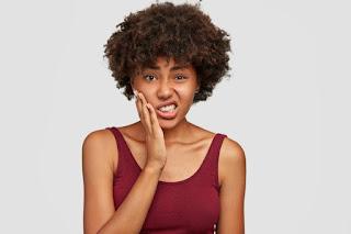 mulher negra fazendo careta forçando a pele