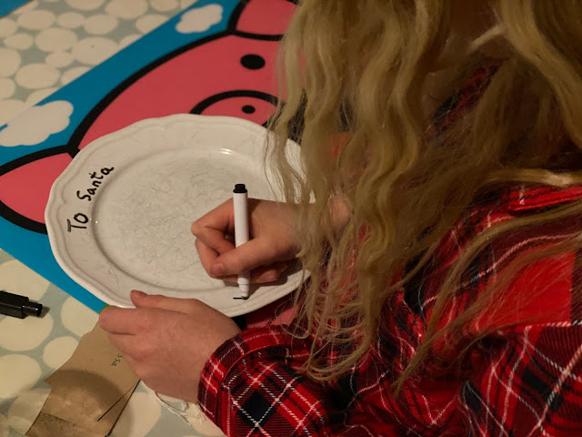 "A girl with long hair writing "" To Santa"" on a plate"