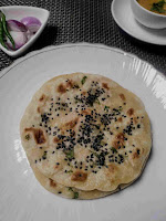 Serving kulcha in a plate, dal and onion slices in background