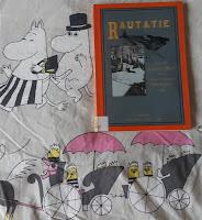 Rautatie-kirja, taustalla iloiset Muumimamma ja Muumipappa sekä vaunut