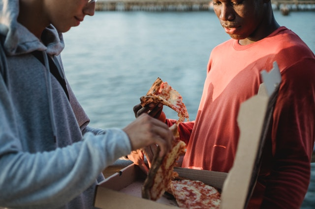 young men sharing pizza