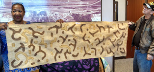 Teresa R.Kemp showing Wall hanging from Ghana Africa  with Hebrew characters on it at the Cornbread Festival