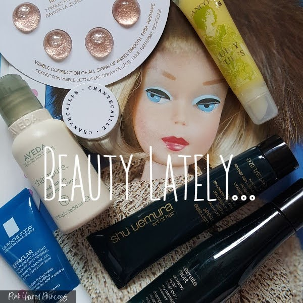 beauty products sitting against Barbie doll face backdrop with Beauty Lately title in white lettering over the top