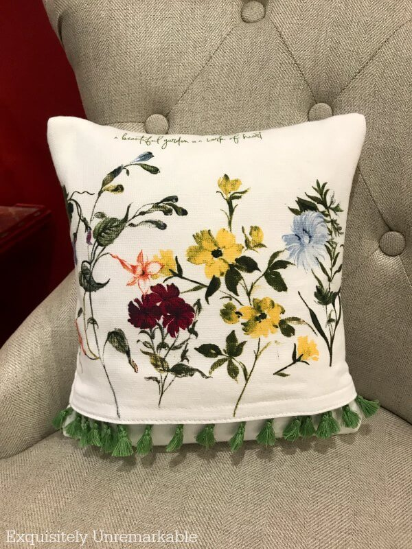 Floral fringed DIY dish towel pillow on a chair