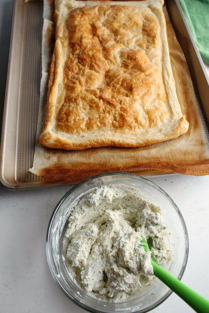 prebaked puff pastry sheet next to bowl of herbed ricotta ready to put together tomato tart