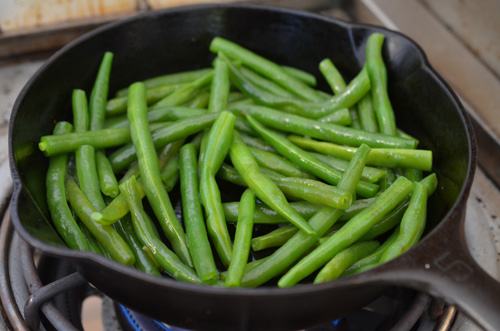 Green beans cooking in a Griswold #5 Cast Iron Skillet on a Saber Elite 3 burner grill
