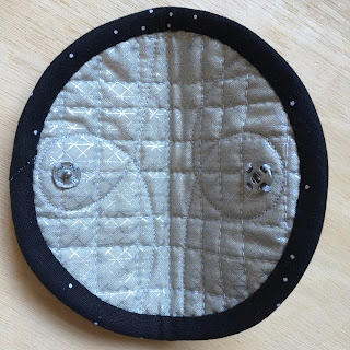 inside of quilted circle with snap fasteners sewn on either side below binding