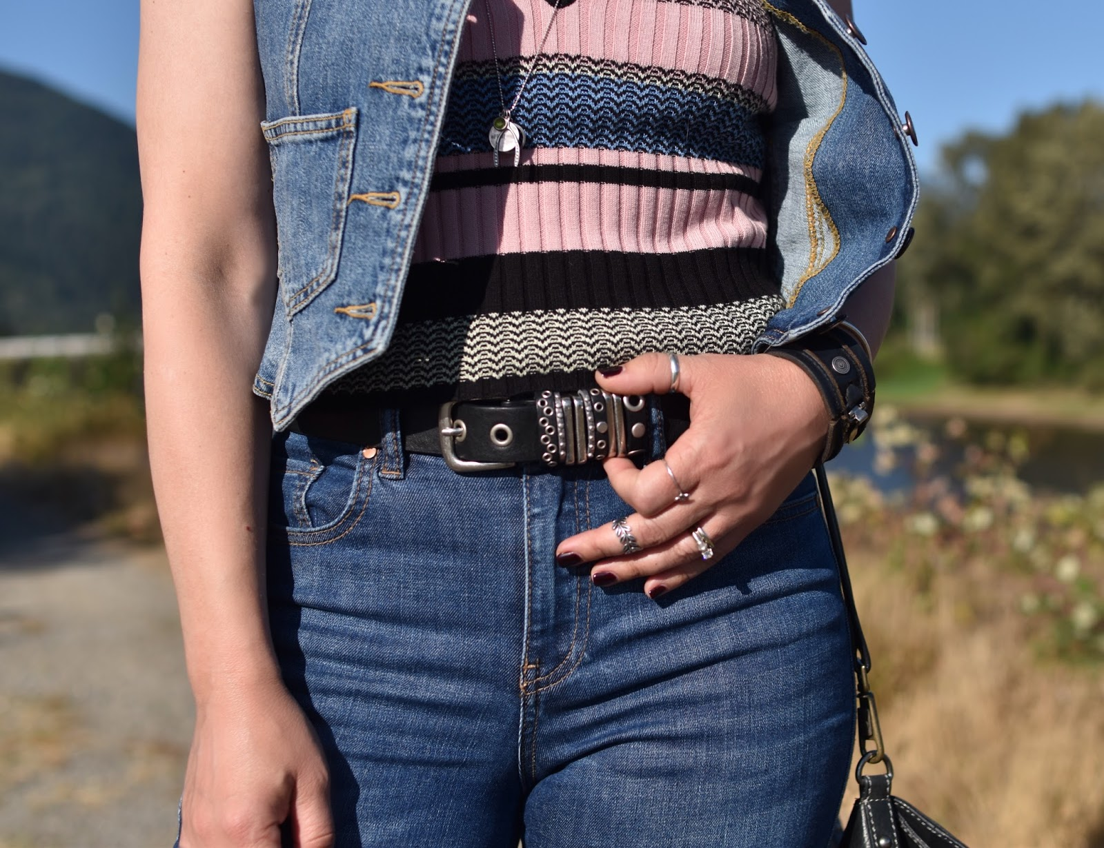 Monika Faulkner outfit inspiration - jeans, striped tank top, denim vest, stud-embellished belt