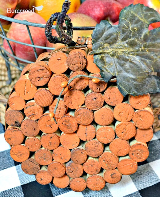 Orange painted cork circle with leaf and stem