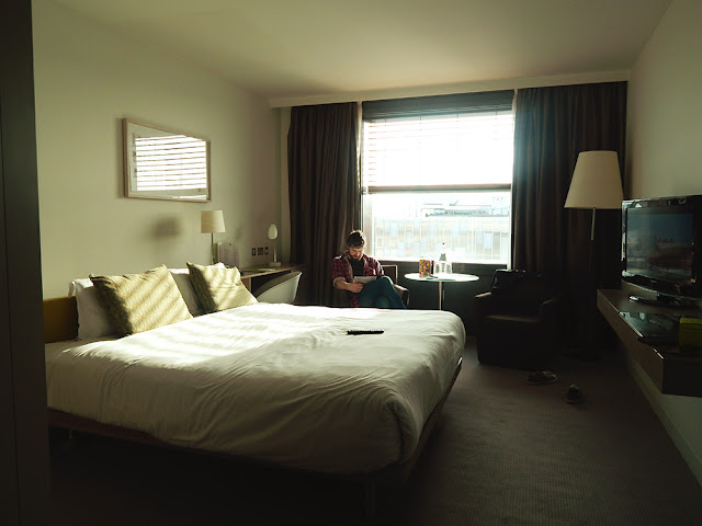 Hotel room with a man sitting a reading a magazine