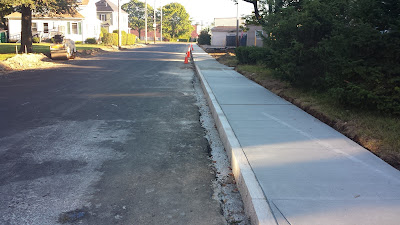 new base coat in place, the curbing and sidewalks are being installed before the final coat is applied on Lewis St