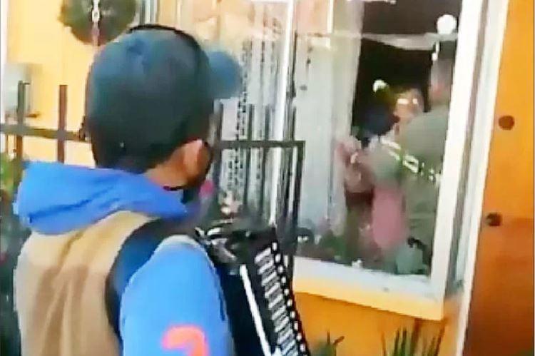 Hijo toca el acordeón para sus padres desde la ventana