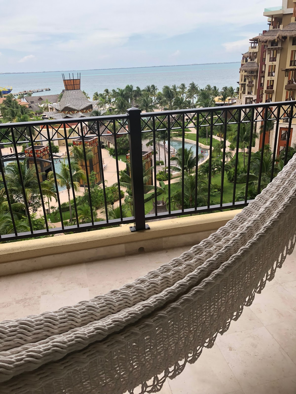 a porch hammock is in the front of the shot with the entire resort behind it, there is a pool closer to the hotel, and the ocean in the back