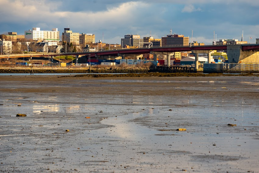 Portland, Maine USA April 2020 photo by Corey Templeton. Clearing clouds above the Portland skyline at low tide.