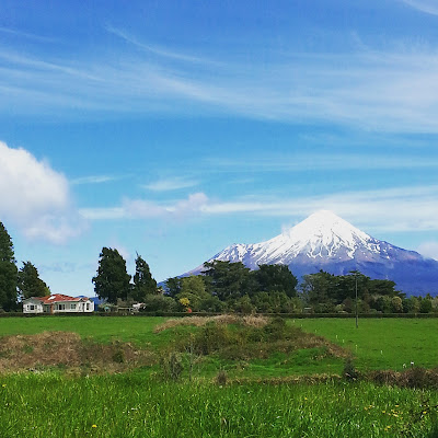 A farmhouse with Mount Taranaki in the background.