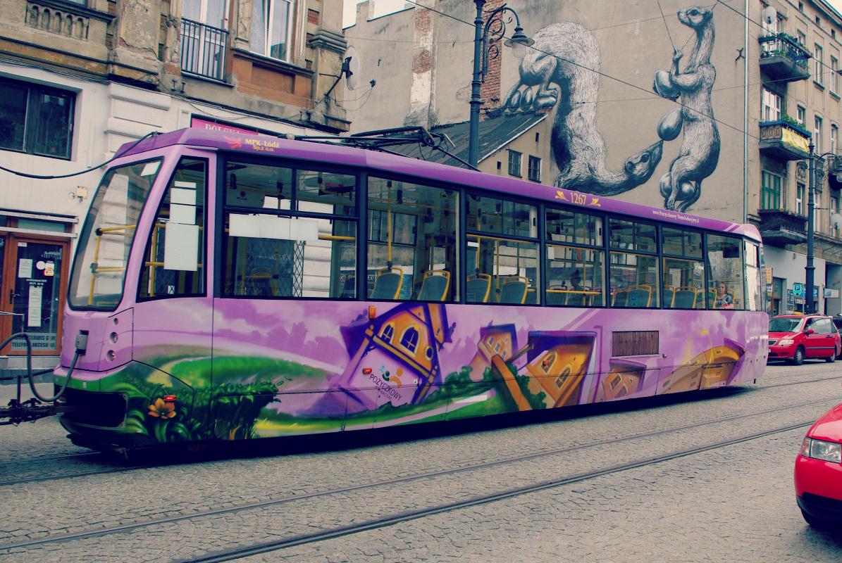 Łódź  - kolorowy tramwaj z muralem w tle.
