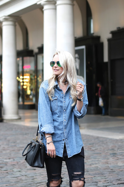 a blogger poses in covet garden wearing ripped jeans, denim shirt and prada double zip handbag