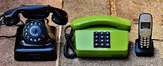 Three landline telephones rest on a stone surface. On the left is a black rotary dial phone, in the middle a lime green push-button touchtone phone, and on the right a digital cordless phone rests in its cradle.