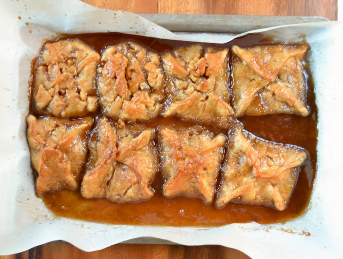 Apple Dumplings In Caramel Cinnamon Syrup on a parchment paper lined baking sheet sitting on a wooden board.