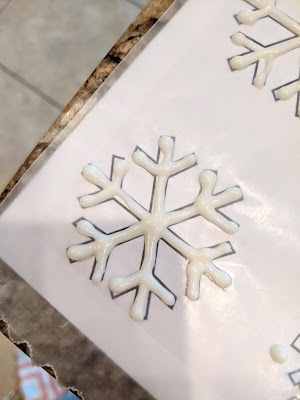 Piped Almond Bark onto Snowflake Shape under Wax Paper