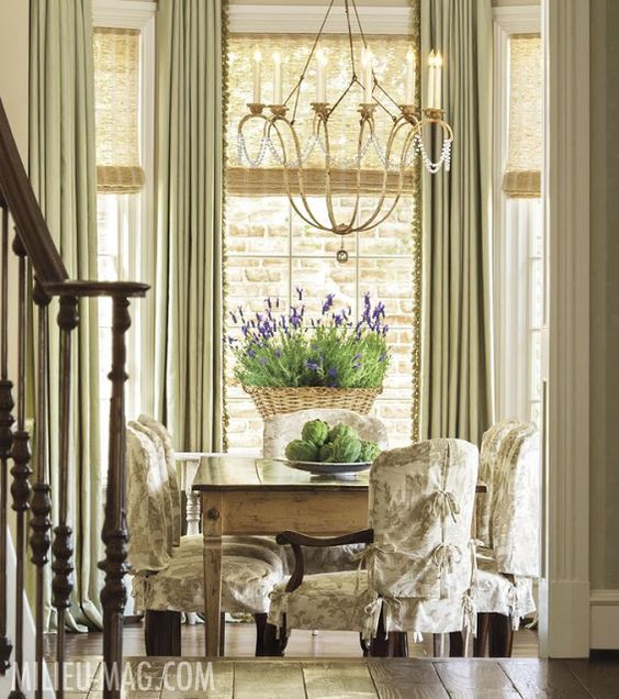 French Country dining room with farm table and slipcovered chairs in Milieu magazine