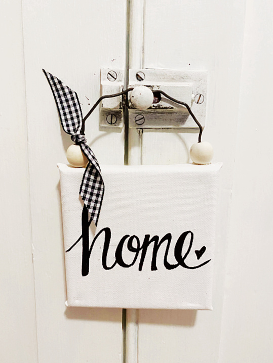 home sign hanging on a door