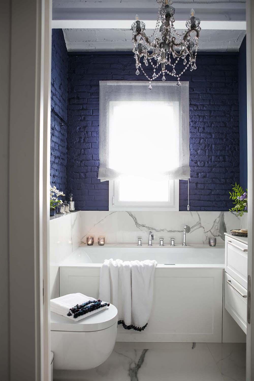 Baño de estilo retro industrial con pared de ladrillo pintada.