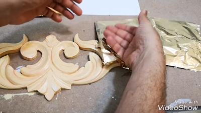 تطبيق ورق الذهب برفق بواسطة ظهر اليد على سطح وحدة خشبية نباتية