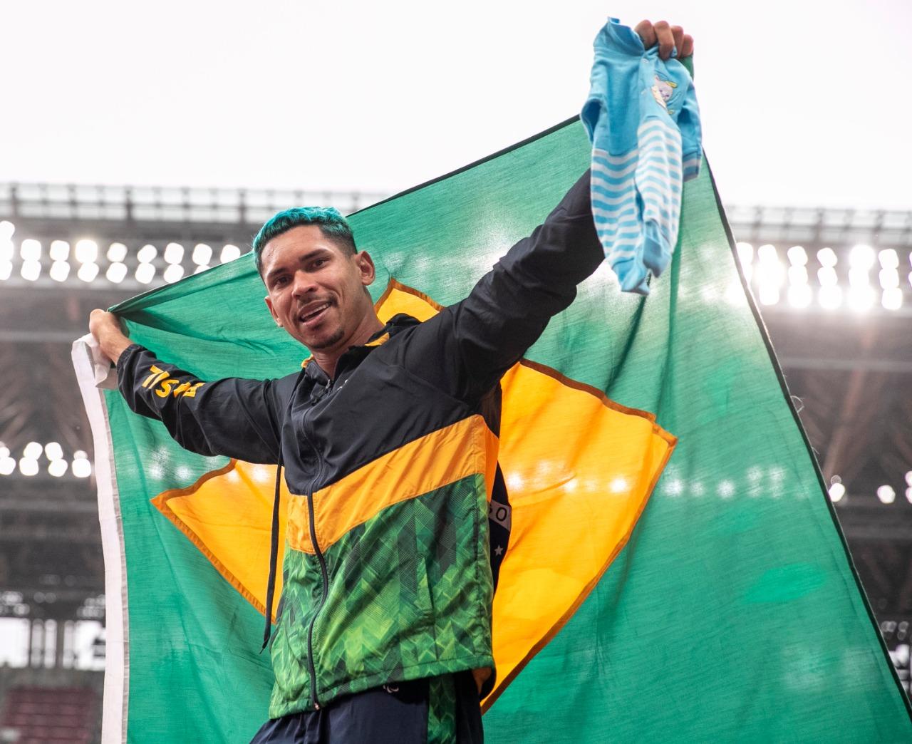 Mateus Evangelista, de uniforme e cabelo verde, com bandeira gigante do Brasil