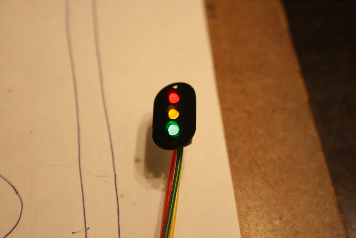 Trackside signal face with red, green, and yellow LEDs attached to power leads