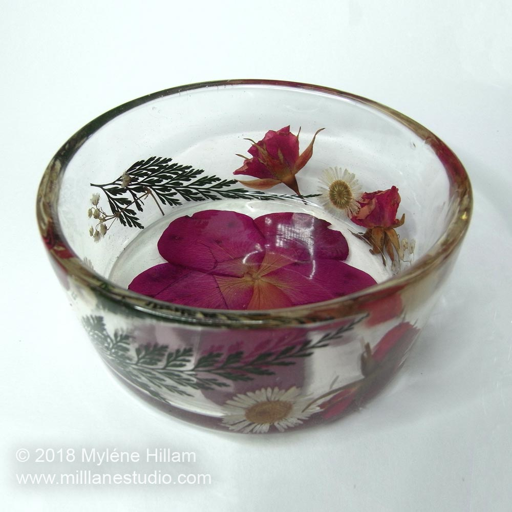 Dried flowers embedded in the walls of a clear epoxy resin trinket dish.