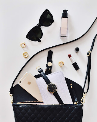 black purse with phone watch and cosmetics spilling out