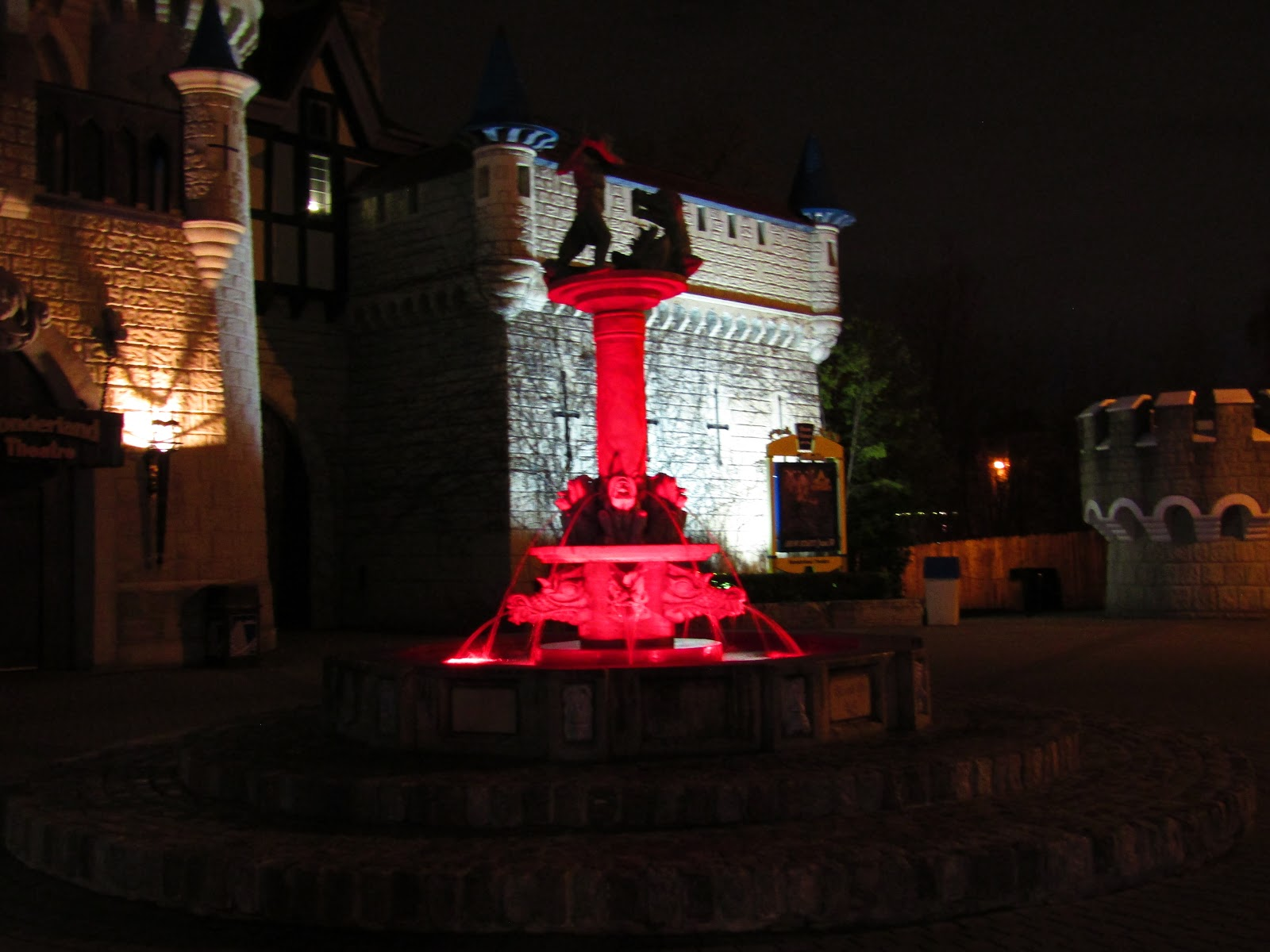 The Medieval Faire Fountain illuminated by red lights at night.