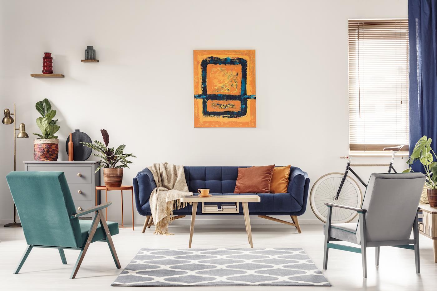 Sofá de respaldo bajo tapizado en capitoné con mesa baja en madera clara