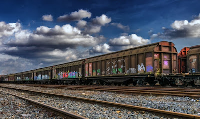 Several rail cars transporting some goods, the cloudy sky above them