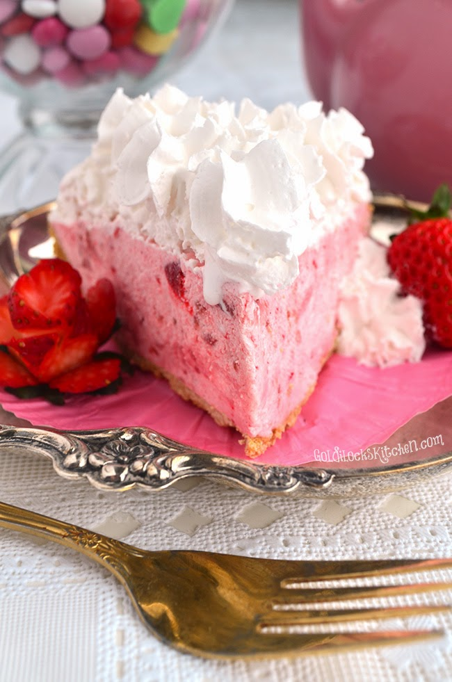 A slice of Easy Three Step Strawberry Cream Pie sits on a decorative plate garnished with strawberries and whipped cream - The Goldilocks Kitchen