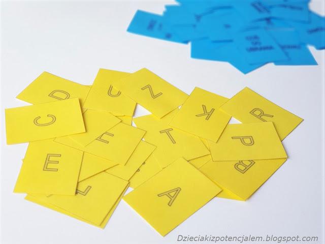 Na zdjęciu widać karty do gry diy Pastwa Miasta, karty zostały wydrukowane i zalaminowane, na pierwszym planie widać żółte karty z literami a na drugim niebieskie z kategoriami