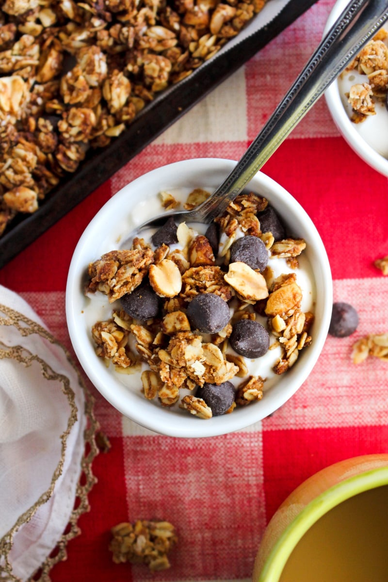 Top view of a white bowl of yogurt topped with Chocolate Chip Peanut Butter Granola on a red and white checkered background.