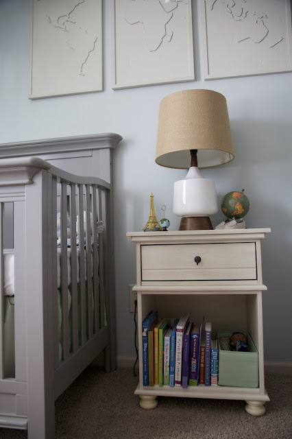 A travel and adventure-inspired gender neutral nursery with pops of pale gray, white, blue, and pale green.