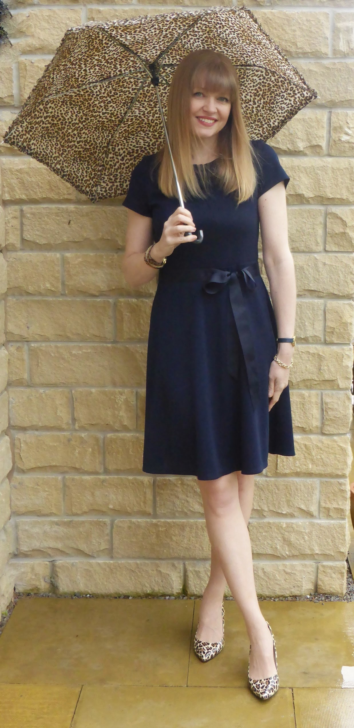 What LIzzy Loves, over 40 fashion blogger wears navy jersey dress with ribbon belt, leopard shoes, leopard heels, leopard umbrella