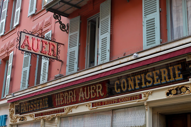 Terracotta washed walls, sea green painted wooden shutters and gold glass lettering in a patisserie.