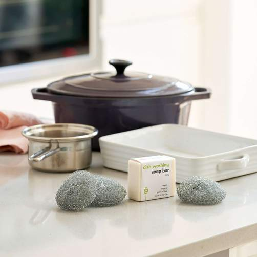 eco friendly steel scouring pads on a white kitchen island with pots and pans