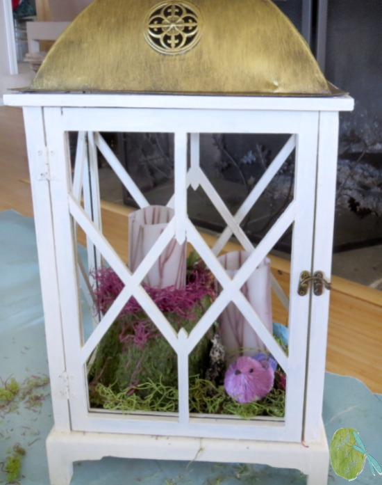 Lantern in progress with tarp, green moss, straw bird, twig candles, moss flower pot