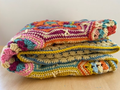 Folded up colourful crochet blanket
