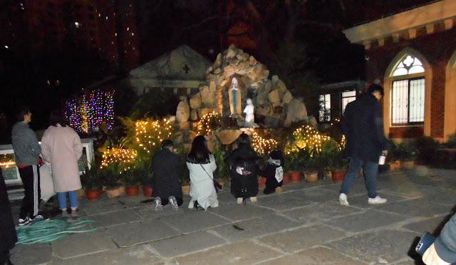 外のマリア像に祈っている家族