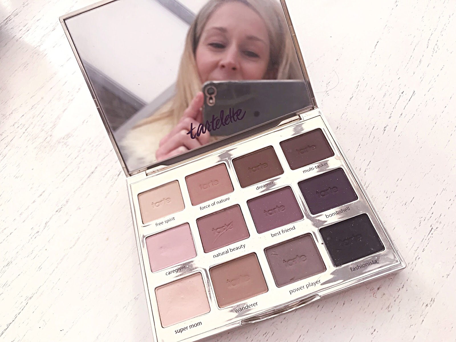 Eyeshadow Palette with a reflection of a girls face in the mirror