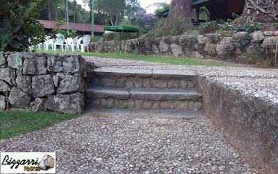 Muro de pedra com a pedra rachão, tipo de pedra cortada a mão em tamanhos irregulares. Muro de pedra rachão com a escada de pedra folheta e o caminho com pedras tipo pedregulho de rio.