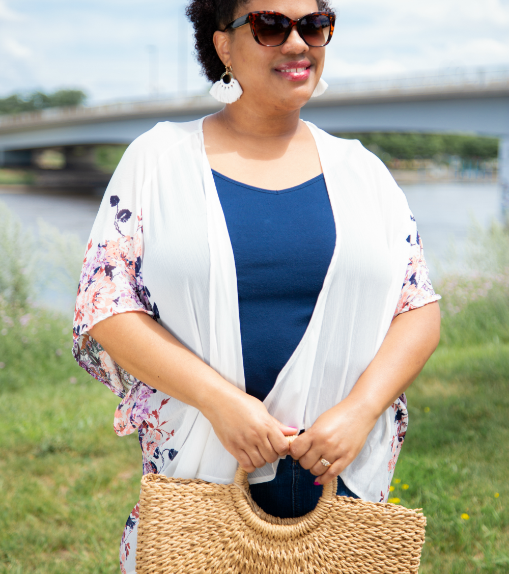 a woman standing by a river holding a straw purse