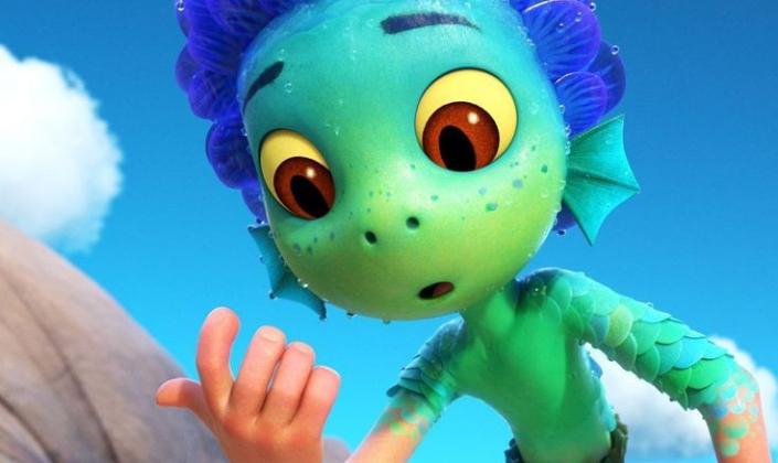 Imagem: Animação 3D. Luca é um ser aquático, tem a cabeça feita de escamas verdes, seus olhos são grandes e amarelos e possui dois buracos no lugar de nariz. No lugar de cabelo tem escamas azuis levatadas para cima e no pescoço tem guelras. Seu corpo está metade humano e ele olha espantado para sua mão que é humana agora.
