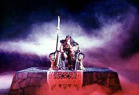 """Cette image est tirée du film """"Conan le Barbare"""", """"Conan the Barbarian"""" en version originale, réalisé en 1982 par John Milius. On peut y voir Conan interprété par le musculeux et charismatique Arnold Schwarzenegger siégeant sur ce qui semble être un trône. Il tient son menton avec sa main gauche et inspire le respect par sa pose empreinte de sérénité et de puissance. Le fond orageux et vie ajoute à cette impression de noblesse puissante. Cette image illustre très à propos le poème """"Roi sans couronne"""" du Marginal Magnifique dans lequel le grand poète explique brillamment qu'il souhaite être roi par sa noblesse d'âme et son attitude digne face à la vie, l'adversité. Pas besoin de richesses ni de gloire pour s'élever au-dessus de la masse, il suffit d'avoir du panache en somme."""